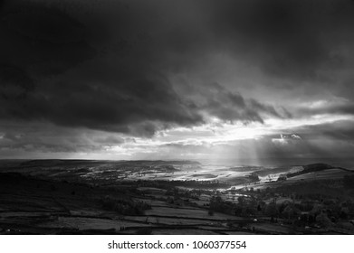 Stunning black and white sunbeams over Big Moor in the Peak District landscape in Autumn