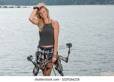 Stunning blonde female Caucasian archer poses with her compound bow near a lake