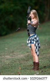 Stunning blonde female Caucasian archer shoots an arrow from a compound bow - arrow seen flying down range