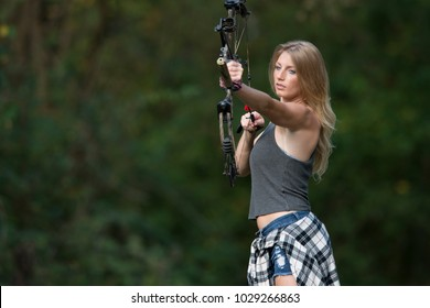 Stunning blonde female Caucasian archer shoots an arrow from a compound bow