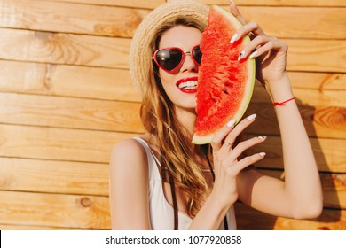 Stunning blonde girl chilling in summer day and eating watermelon. Close-up portrait of laughing european lady in boater and sunglasses fooling around on wooden background.
