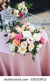 Stunning bouquet of roses stands on table with pink cloth