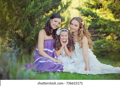 Stunning Brunette blond chestnut blue eyes sisters girls wearing stylish white purple dress enjoying life time together summer sunny day in garden forest on green grass happy smiling.