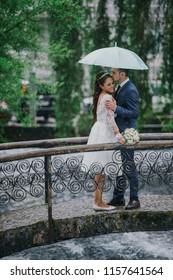Stunning brunette bride leans to a groom standing under an umbrella