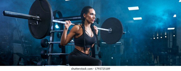 Stunning brunette female with long braids doing squats using barbell, panoramic. Side view of concentrated fitnesswoman with perfect muscular body training legs in gym in dark smoky atmosphere.