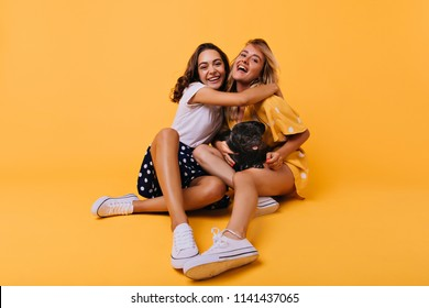 Stunning brunette girl in white shoes embracing her sister with happy smile. Carefree blonde lady having fun with best friend and bulldog during photoshoot on yellow background.
