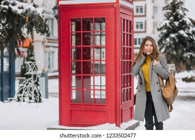 Stunning brunette woman in yellow cardigan standing near british call-box in winter day. Outdoor photo of adorable girl in trendy coat posing beside phone booth with spruce on background.