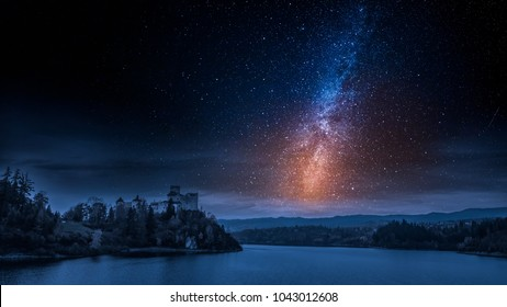 Stunning castle by the lake with milky way at night