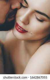 Stunning caucasian girl with red lips is kissed by her bearded lover while embracing each other