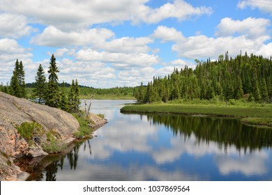 Stunning clear reflection of a beautiful landscape with rocks and tall fir trees on a quiet lake in Ontario, Canada.