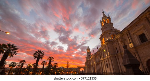 Stunning colorful sky and clouds at dusk in Arequipa, famous travel destination and landmark in Peru. Wide angle view from below of the colonial Cathedral. Panoramic frame.