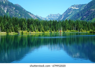 Stunning colors, mostly shades of blue & green, in a beautiful view in the Cascade Mountains of WA state of a line of evergreen trees & mountain peaks all reflected in  blue water of an alpine lake.
