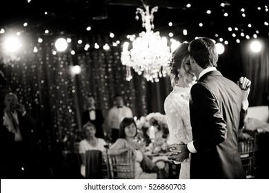Stunning couple dance under rich chandeliers in a restaurant