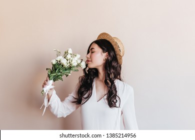 Stunning curly asian woman sniffing white flowers. Studio shot of romantic chinese lady with eustomas.