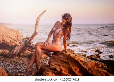 Stunning curly brunette in a white swimsuit posing on the stone shore and looks thoughtfully down. Her hair is wet, her skin is tanned, holidays at sea were successful.