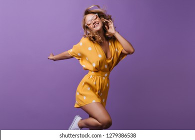 Stunning curly female model jumping on purple background. Indoor photo of slim girl in bright yellow dress.