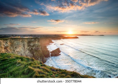 Stunning dramatic sunset from cliffs over Whipsiderry Beach at Porth in Newquay, Cornwall