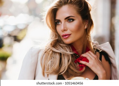 Stunning european girl with glamorous make-up looking away touching her red scarf. Close-up portrait of beautiful fair-haired woman with blue eyes relaxing on blur background.