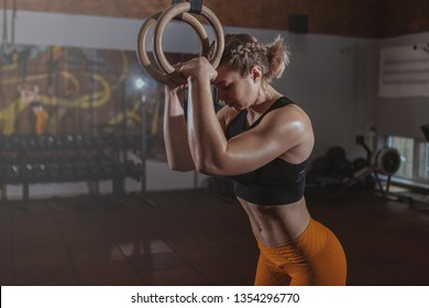 Stunning female athlete resting after exercising on gymnastic rings at the gym, copy space. Powerful sportswoman preparing to workout on gymnastic rings