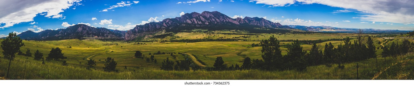 Stunning Flatirons mountain and valley with winding road on a summer day with blue sky and clouds, Boulder, Colorado