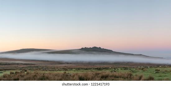 Stunning foggy sunrise landscape over the tors in Dartmoor revealing peaks through the mist