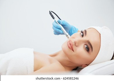 Stunning girl with brown hair fixed behind,clean fresh skin naked shoulders wearing white bath robe and hair wrap, doing cosmetic procedure, close up, microdermabrasion.