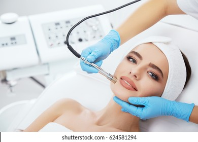 Stunning girl with brown hair fixed behind,clean fresh skin naked shoulders wearing white bath robe and hair bandage, doing cosmetic procedure at light medical background, microdermabrasion.