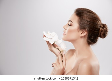 Stunning girl with nude make up and naked shoulders posing at grey background with flower, skin care concept, beauty photo, close up portrait.