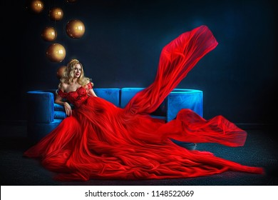 Stunning girl in red long dress, and with diadem, sitting on blue couch