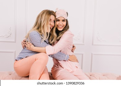 Stunning girls embracing in morning. Indoor shot of lovely ladies posing in pajamas.