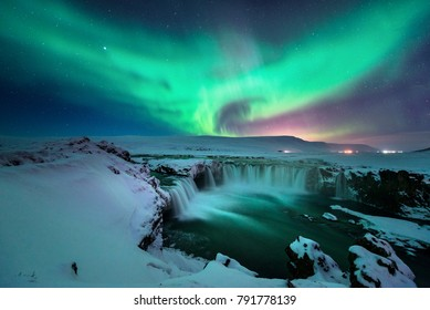 A stunning glowing aurora shape like phoenix bird appears above the landscape of Godafoss waterfall in winter Iceland