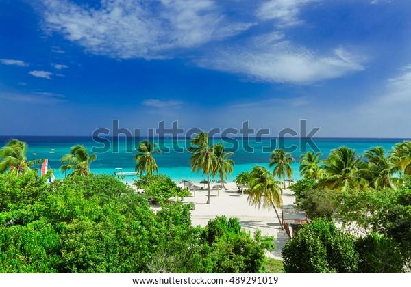atemberaubende schöne, wunderbare Aussicht auf den tropischen Strand der Provinz Holguin und den ruhigen, türkisblauen Ozean auf blauem Himmelshintergrund