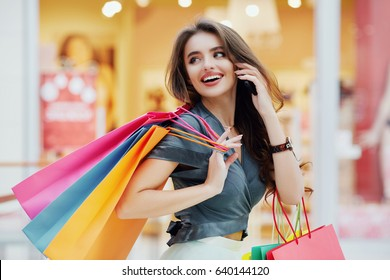 Stunning Happy girl with long brown hair standing with colorful shopping bags and talking on mobile phone, shopping concept, portrait, smiling, looking back.