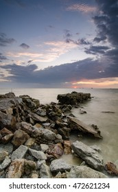 stunning image during sunset at the coastline. abandon concrete structure on the water, dramatic dark clouds with sunlight
