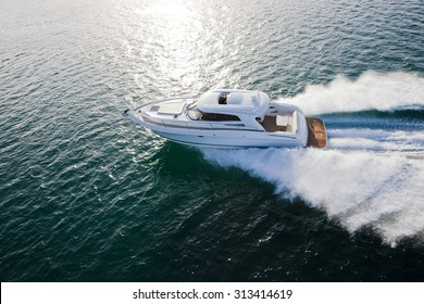 Stunning image of a luxurious boat racing through the ocean in sunlight