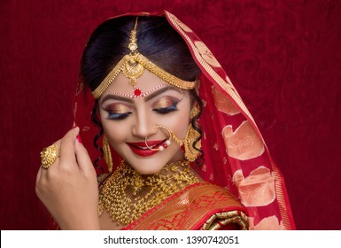 Stunning Indian bride dressed in Hindu red traditional wedding clothes sari embroidered with gold jewelry and a veil smiles tender