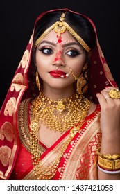 Stunning Indian bride dressed in Hindu red traditional wedding clothes sari embroidered with gold jewelry and red lipstick.