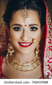 Stunning Indian bride dressed in Hindu traditional wedding clothes lehenga embroidered with gold and a veil smiles tender