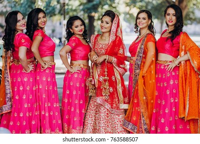 Stunning Indian bride dressed in Hindu traditional wedding clothes lehenga embroidered with gold and a veil stands with her bridesmaids in pink saris pose outside