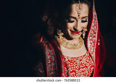 Stunning Indian bride dressed in Hindu red traditional wedding clothes lehenga embroidered with gold and a veil smiles tender standing in the shadow