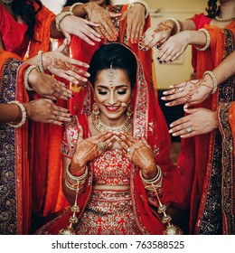 Stunning Indian bride dressed in Hindu traditional wedding clothes lehenga embroidered with gold and a veil sits on the chair while bridesmaids hold their hands with henna tattoos around her