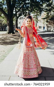 Stunning Indian bride dressed in Hindu traditional wedding clothes lehenga embroidered with gold and a veil smiles tender posing outside