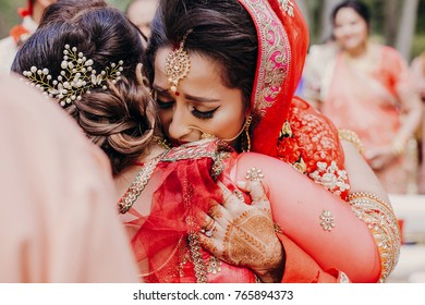 Stunning Indian bride dressed in Hindu traditional wedding clothes lehenga embroidered with gold and a veil during Saptapadi ceremony cries hugging with her mother