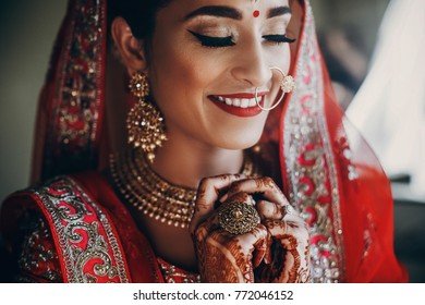 Stunning Indian bride dressed in Hindu red traditional wedding clothes lehenga embroidered with gold and a veil smiles tender holding her hands together