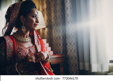 Stunning Indian bride dressed in Hindu red traditional wedding clothes lehenga embroidered with gold and a veil