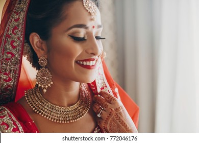 Stunning Indian bride dressed in Hindu red traditional wedding clothes lehenga embroidered with gold and a veil smiles tender