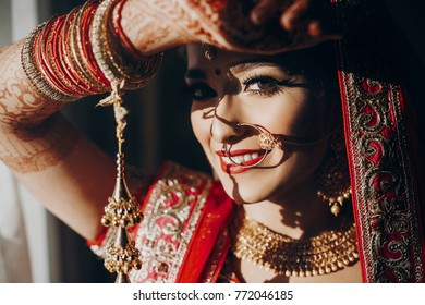 Stunning Indian bride dressed in Hindu red traditional wedding clothes lehenga embroidered with gold and a veil smiles tender hiding her face behind the hand