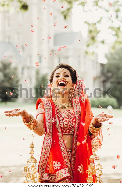 Stunning Indian bride dressed in Hindu traditional wedding clothes lehenga embroidered with gold and a veil smiles tender posing outside with golden accessories under the rain of petals