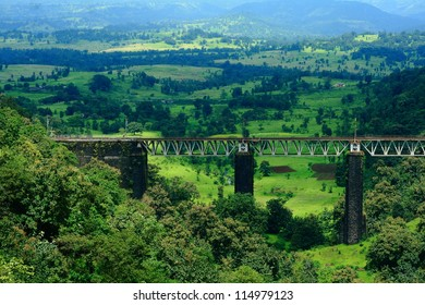 A stunning Indian landscape with a small railway bridge surrounded by greenery and mountains.
