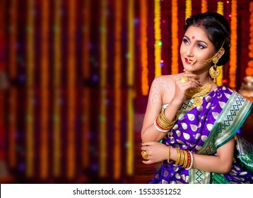 Stunning Indian married woman dressed in Hindu traditional wedding clothes sari embroidered with gold jewelry and a veil smiles tender with extra copy space , Diwali festival concept with young model